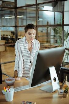 Pantalla de computadora. próspera empresaria mirando a la pantalla de la computadora mientras lee una carta comercial