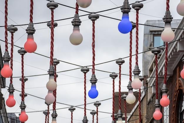 Una pantalla decorativa de grandes bombillas colgando sobre la intersección de ganton street y carnaby street en soho