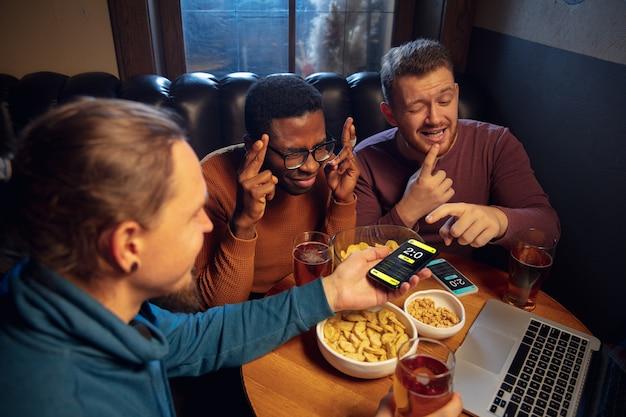 Pantalla del dispositivo con aplicación móvil para apostar y marcar. dispositivo con los resultados del partido en la pantalla, aficionados emocionados en segundo plano durante el partido.