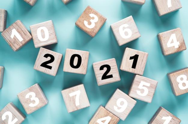 Pantalla de impresión del año 2021 en cubo de madera, entre otros, número sobre fondo azul.