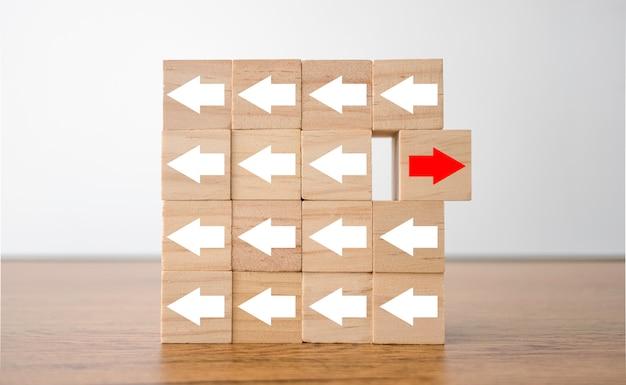 Pantalla de impresión de flecha roja en cubo de madera cambiando de dirección con flecha blanca.