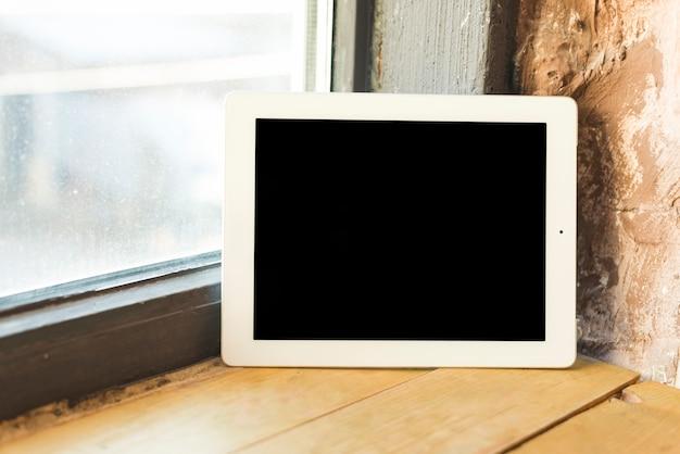 Pantalla negra con tableta digital en el alféizar de la ventana.