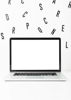 Pantalla de ordenador portátil en blanco con alfabetos dispersos sobre fondo blanco