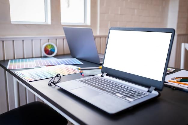 Pantalla de portátil blanco en blanco de diseñadores gráficos en mesa de escritorio en colaboración