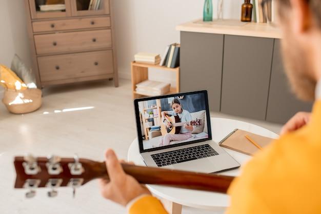 Pantalla de portátil con diligente adolescente tocando la guitarra mientras está sentado en el sofá en el hogar durante la lección en línea con el maestro