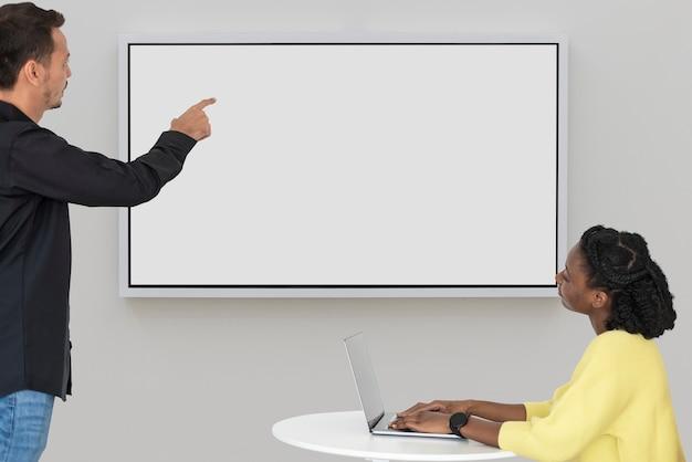 Pantalla de proyección en blanco con colegas en una reunión de tecnología inteligente