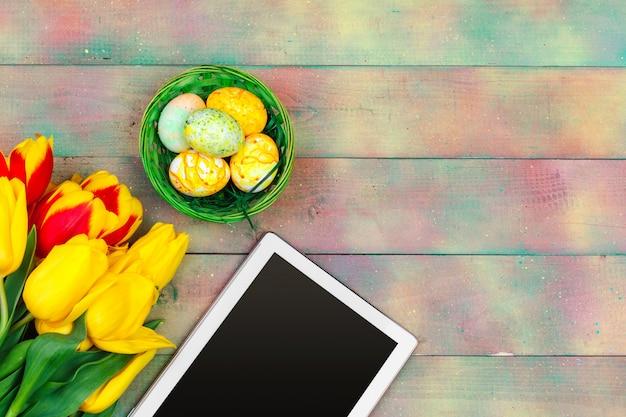 Pantalla de tableta para mensaje y coloridos tulipanes y huevos de pascua en madera