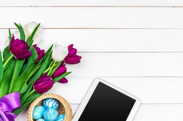 Pantalla de tableta para mensaje y coloridos tulipanes y huevos de pascua sobre fondo de madera