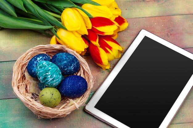 Pantalla de tableta para mensaje y coloridos tulipanes y huevos de pascua