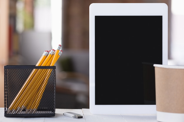 Pantalla de tableta negra vacía en la pared borroneada con lápices y una taza de café. copyspace, espacio negativo para su publicidad, estilo oficina.