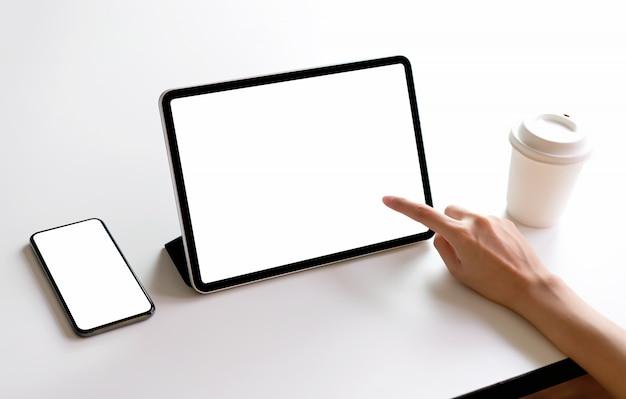 Pantalla de tableta y teléfono inteligente en blanco en la maqueta de la mesa para promocionar sus productos.