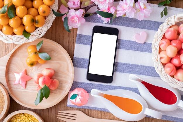 Pantalla de teléfono inteligente en blanco con frutas de imitación deletable, frutas en forma de frijol mungo