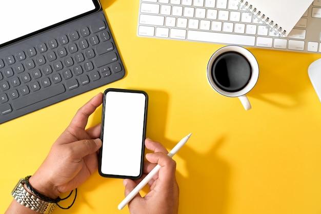 Pantalla de teléfono móvil en blanco en la mano del hombre sobre el escritorio de oficina