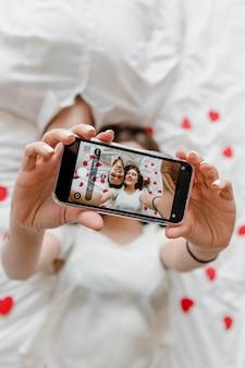 Pantalla del teléfono con selfie de hombre y mujer enamorados besándose en la cama