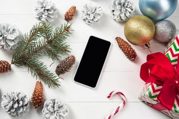 Pantalla vacía en blanco del teléfono inteligente en la pared de madera blanca con decoración y regalos coloridos de vacaciones.