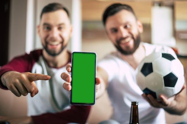 Pantalla verde en blanco en el teléfono inteligente en la mano de emocionados jóvenes fanáticos del deporte barbudo. ganar en apuestas