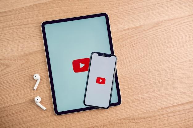 La pantalla de youtube en el iphone de apple en la mesa, youtube es el popular sitio web para compartir videos en línea.