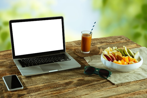 Pantallas en blanco de la computadora portátil y el teléfono inteligente en una mesa de madera al aire libre con la naturaleza en la pared frutas y jugo fresco cercano. concepto de lugar de trabajo creativo, negocio, autónomo. copyspace.
