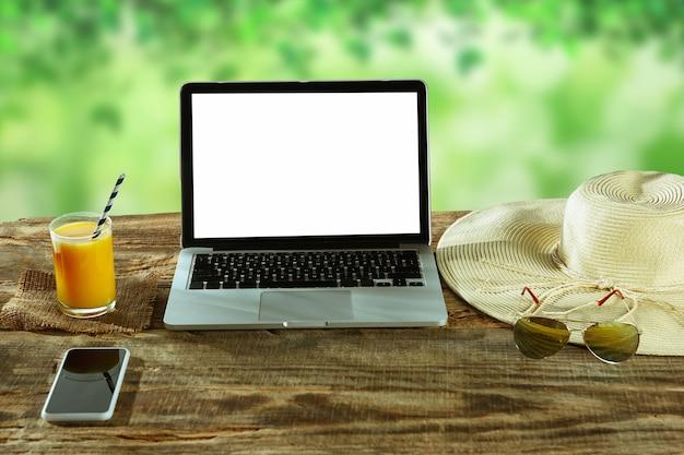 Pantallas en blanco de la computadora portátil y el teléfono inteligente en una mesa de madera al aire libre con la naturaleza en la pared vasos y jugo fresco cerca. concepto de lugar de trabajo creativo, negocio, autónomo. copyspace.