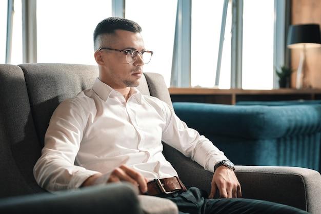 Pantalón con cinturón. hombre guapo con estilo joven vestido con pantalones cuadrados con cinturón de cuero sentado en un sillón