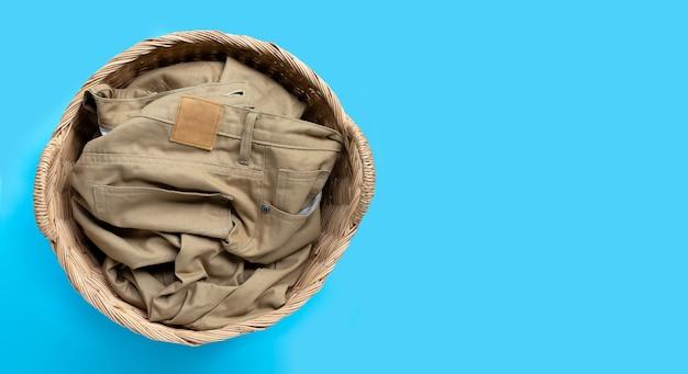 Pantalones en canasta de lavandería sobre fondo azul. copia espacio