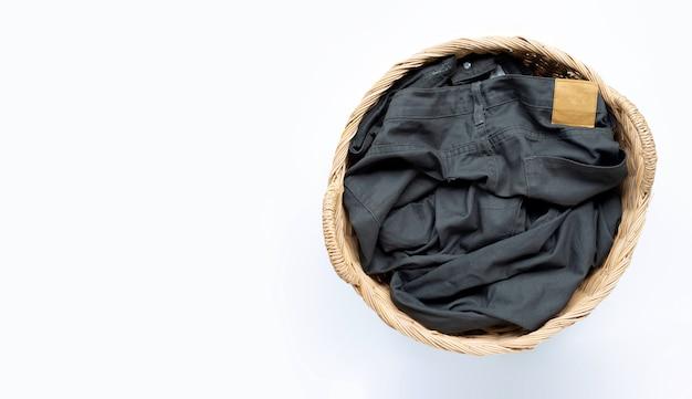 Pantalones en canasta de lavandería sobre superficie blanca. copia espacio