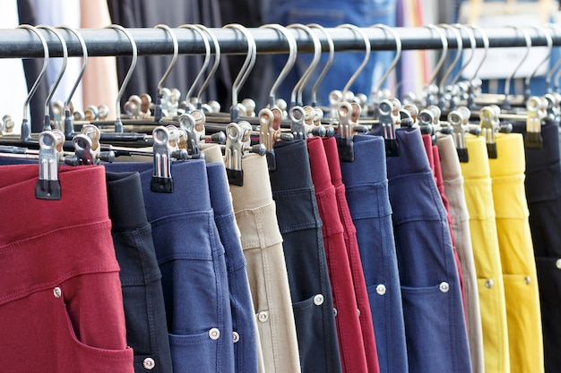 Pantalones casuales multicolores colgando de percha de cerca, vista lateral