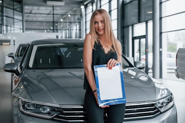 En pantalones negros. chica y coche moderno en el salón. durante el día en interiores. comprar vehículo nuevo