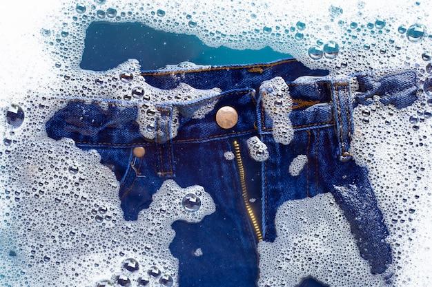 Los pantalones vaqueros se sumergen en detergente en polvo con disolución de agua. concepto de lavandería