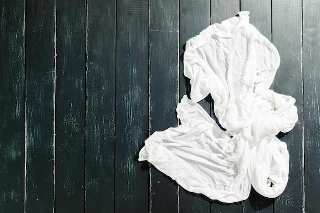 Pañuelo blanco sobre mesa de madera negra.