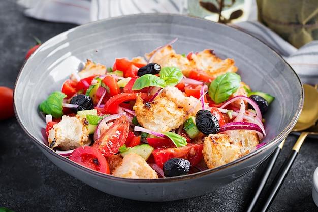 Panzanella toscana, ensalada italiana tradicional con tomate y pan. ensalada de panzanella vegetariana. comida sana mediterránea.