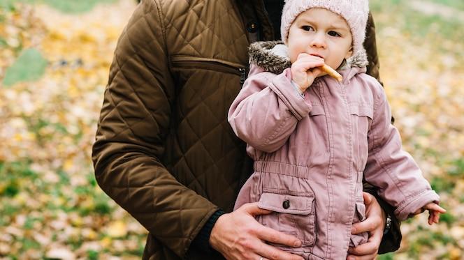 Papá abrazando a su hija cuando ella come galleta en el bosque de otoño