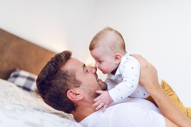 Papá acostado en la cama en el dormitorio y levantando a su amoroso bebé riendo
