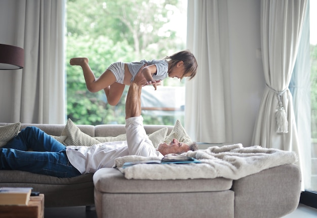 Papá acostado en el sofá y levantando a su hijo en el aire bajo la luz del sol a través de las ventanas