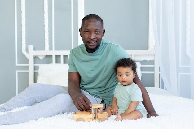 Papá afroamericano con hijo jugando en la cama en casa con un coche de juguete de madera, familia feliz