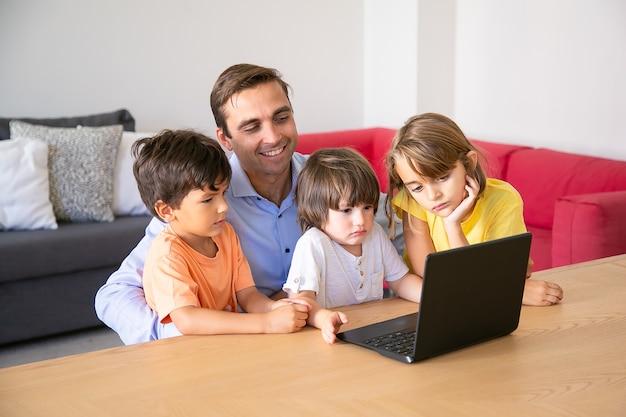Papá alegre y niños pensativos viendo películas a través de la computadora portátil juntos durante el fin de semana. padre feliz sentado a la mesa con los niños en la sala de estar. concepto de paternidad, infancia y tecnología digital.