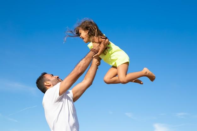 Papá alegre sosteniendo a niña emocionada y levantando las manos en el aire