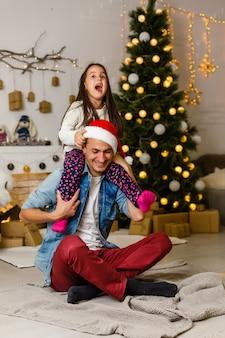 Papá amoroso con hija sobre sus hombros decorando hermoso árbol de navidad