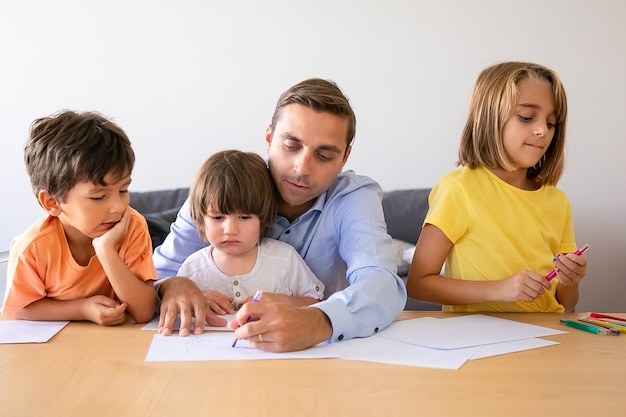 Papá amoroso y niños lindos dibujando con marcador en la mesa. padre caucásico de mediana edad pintando y jugando con niños encantadores en la sala de estar. concepto de tiempo de paternidad, infancia y familia