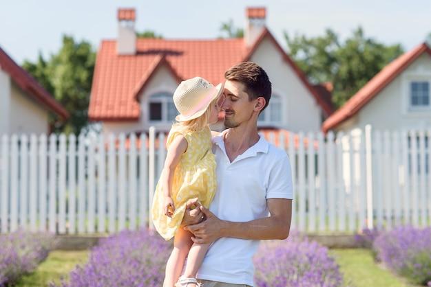 Papá apuesto joven sostiene a su pequeña hija linda en brazos de pie en el jardín de su patio trasero.
