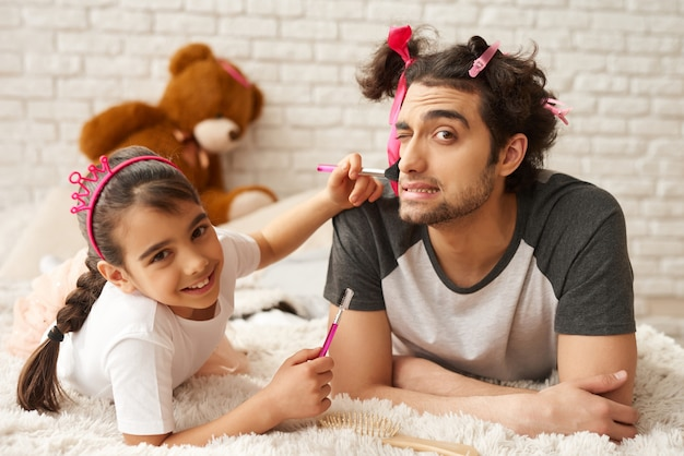 El papá árabe con la hija está poniendo en un sofá.