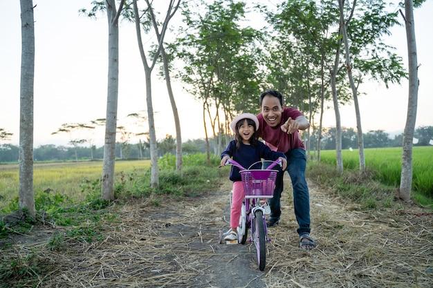 Papá asiático ayudando a su hijo a andar en bicicleta al aire libre