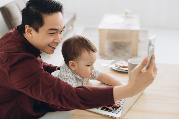 Papá asiático y su pequeño hijo desayunando en la computadora portátil y tomando selfie en el teléfono