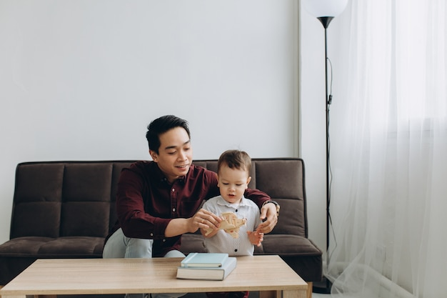 Papá asiático y su pequeño hijo lindo jugando con un avión de madera en una habitación luminosa