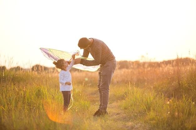 Papá ayuda a su hija a volar una cometa en un campo en el verano al atardecer. animación familiar al aire libre, día del padre, día del niño. zonas rurales, apoyo, asistencia mutua. luz naranja del sol
