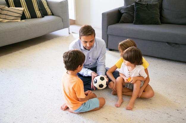 Papá cariñoso sosteniendo la pelota y contando historias a los niños. padre e hijos caucásicos de mediana edad sentados en el suelo en la sala de estar y jugar juntos. concepto de infancia, actividad de juego y paternidad.