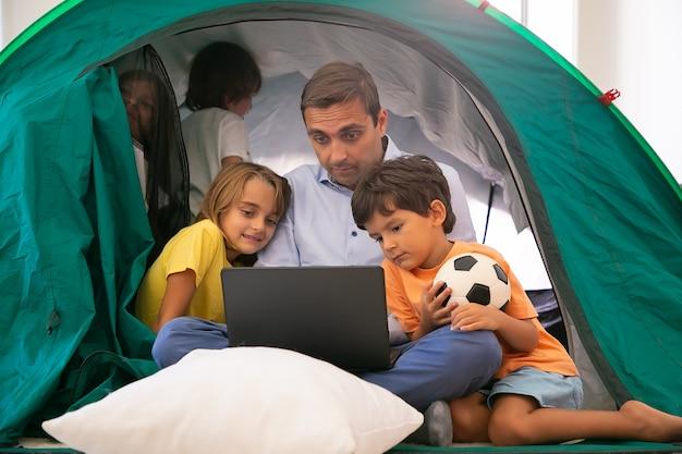 Papá caucásico sentado con las piernas cruzadas con los niños en la carpa en casa y viendo películas a través de la computadora portátil. niños encantadores abrazando al padre, divirtiéndose y jugando. concepto de infancia, tiempo en familia y fin de semana.