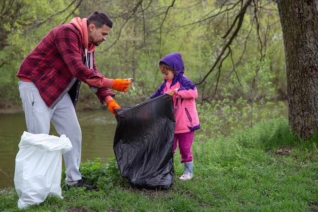 Papá e hija, con bolsas de basura, limpian el ambiente de basura.