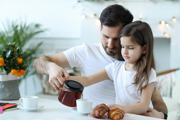 Papá e hija desayunando en la cocina