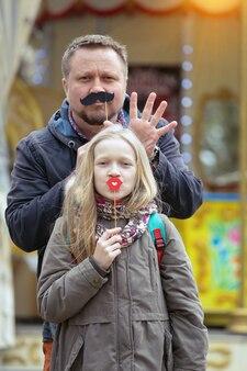 Papá e hija se divierten en el fondo del carrusel francés en parís